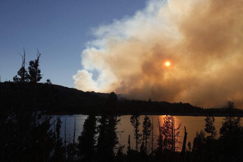 The sun is dimmed by smoke over a lake surrounded by pine trees.