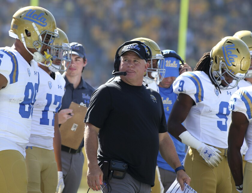 UCLA head coach Chip Kelly walks with his players prior to a game against Arizona State on Nov. 10, 2018.