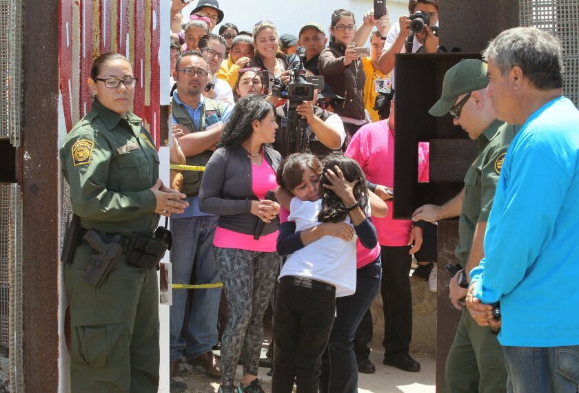Border Patrol Officers stand by as 7 year old Frida Villagomez, of San Diego, hugs her grandmother Yolanda Verona, of Tijuana, at an opening in the fence near the ocean, At far right is Enrique Morones, the founder/director of the Border Angels, the organization the arranged the event.