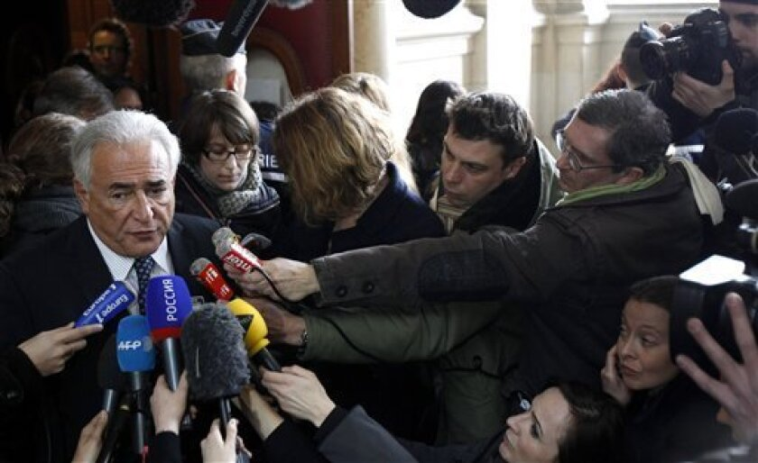 Dominique Strauss-Kahn, left, the former International Monetary Fund chief, addresses the media, as he files a lawsuit over a new book about a past relationship, Tuesday, Feb. 26, 2013,  in Paris. Dominique Strauss-Kahn says he's sick of people trying to exploit his private life to make money. The