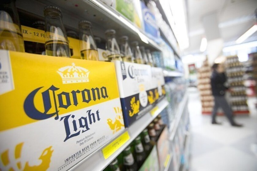 The Justice Department says Anheuser-Busch InBev's bid to buy the shares of Corona maker Grupo Modelo that it doesn't own would give it too much market share in the U.S. Above, a Corona Light display at a New York grocery store.