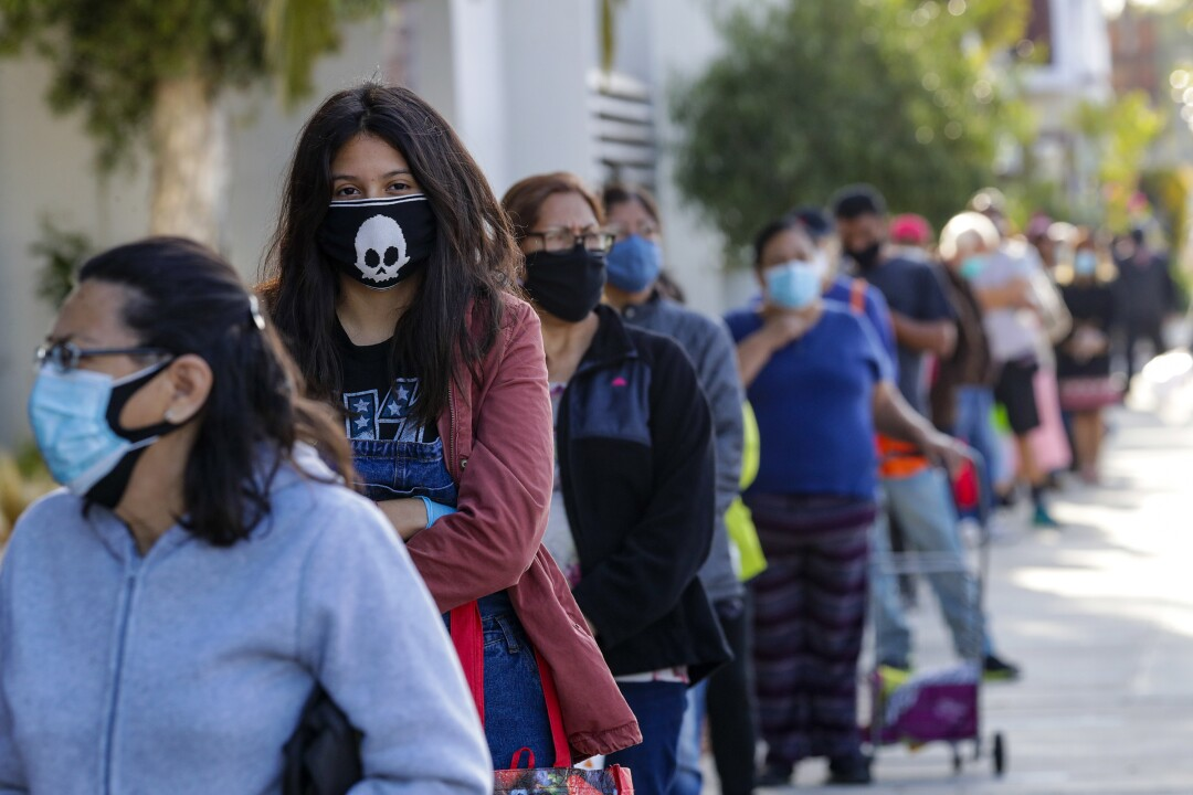 People wait in long line to get meal bags distributed by LAUSD at James A. Garfield High School in Los Angeles.