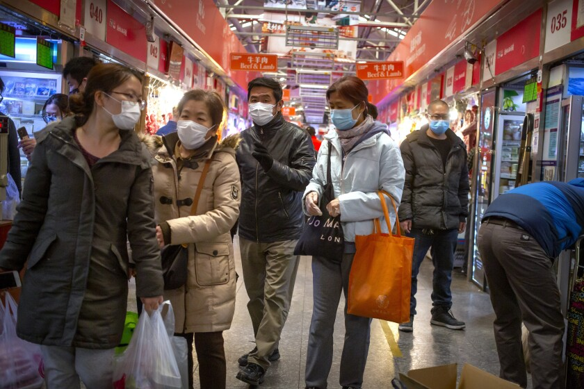 People wear face masks as they shop at a market in Beijing, Saturday, March 14, 2020. The United States declared a state of emergency Friday as many European countries went on a war footing amid mounting deaths as the world mobilized to fight the widening coronavirus pandemic. For most people, the new coronavirus causes only mild or moderate symptoms, such as fever and cough. For some, especially older adults and people with existing health problems, it can cause more severe illness, including pneumonia. (AP Photo/Mark Schiefelbein)