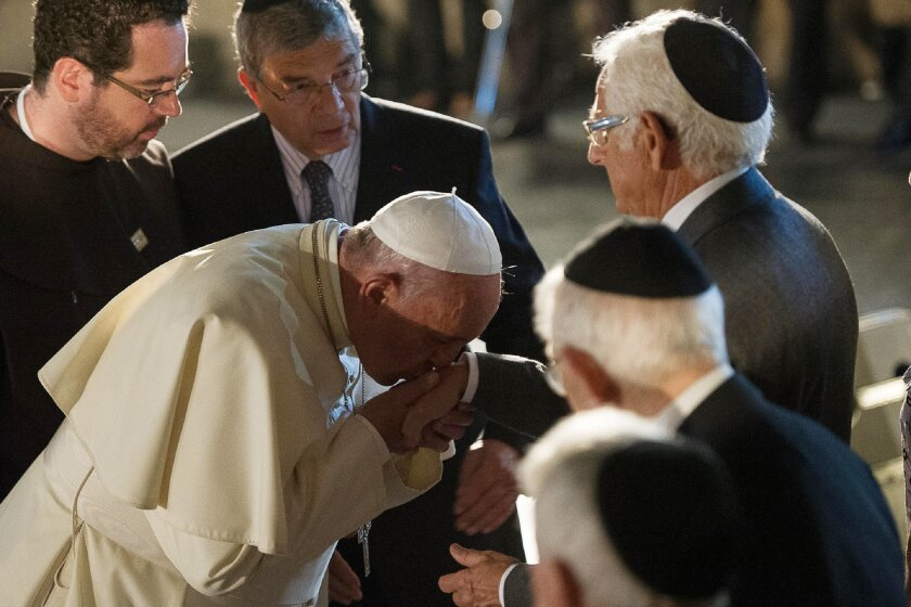 In this photo provided by the Vatican newspaper L'Osservatore Romano, Pope Francis kisses the hand of a Jewish men at the Hall of Remembrance on May 26, 2014, during his visit to the Yad Vashem Holocaust Memorial museum commemorating the six million Jews killed by the Nazis during World War II, in Jerusalem Monday, May 26, 2014. (AP Photo/L'Osservatore Romano, ho)