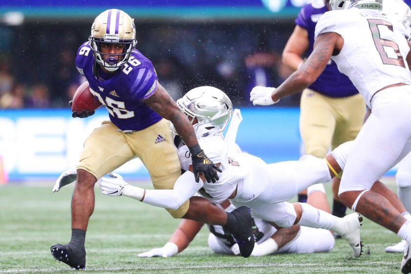 Washington's Salvon Ahmed is tackled by Oregon's Nick Pickett in the first quarter on Saturday in Seattle.