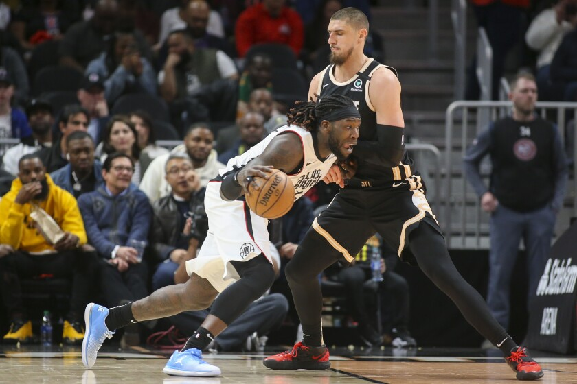 Clippers center Montrezl Harrell tries to drive past Hawks center Alex Len during the first half of a game Jan. 22, 2020, in Atlanta.