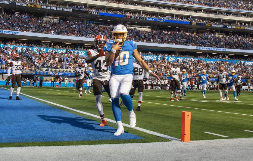 Chargers quarterback Justin Herbert (10) scores in front of Cleveland's John Johnson III (43) on Sunday at SoFi Stadium.