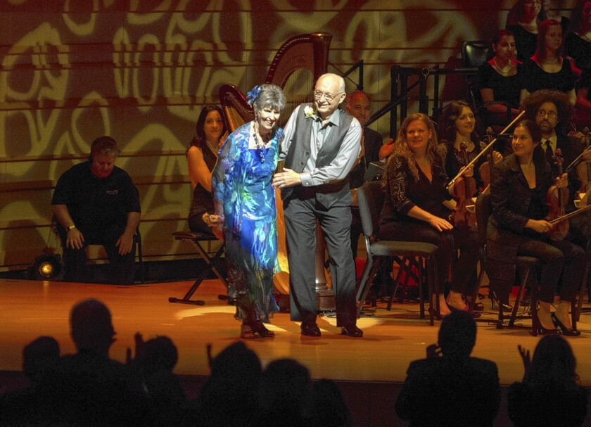 "Nancy Dufault, 72, who has Parkinson's, take a bow after dancing the tango with her husband, Bob, at ""Symphonic Suite for Healing."""