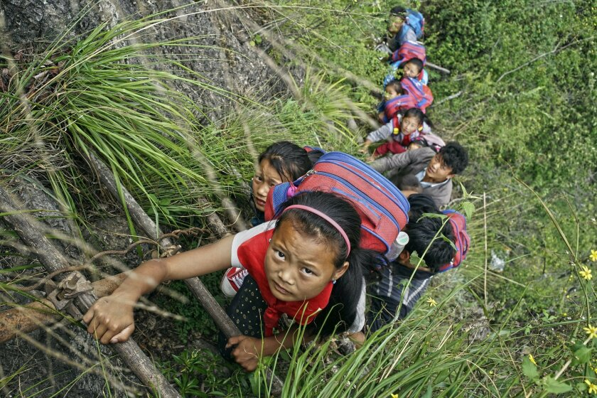 In this May 14, 2016 photo, children wearing their school backpacks climb on a cliff using a bamboo ladder on their way home from school in Zhaojue county, southwest China's Sichuan province. A village in China's mountainous west where schoolchildren must climb an 800-meter (2,625-foot)-high bamboo
