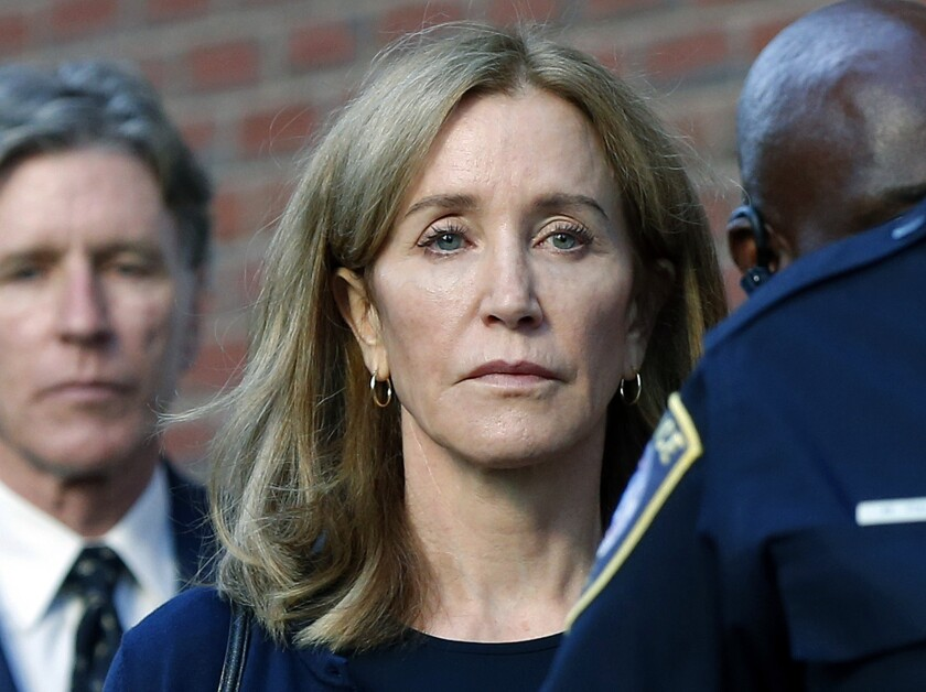 FILE - In this Sept. 13, 2019 file photo, actress Felicity Huffman leaves federal court in Boston with her brother Moore Huffman Jr., left, after she was sentenced in a nationwide college admissions bribery scandal. Huffman was sentenced to 14 days in federal prison in Dublin, Calif., but was released early Friday morning, Oct. 25, after serving 10 days. (AP Photo/Michael Dwyer, File)