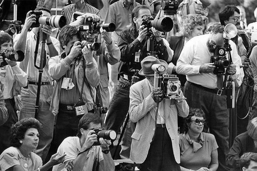 Clem Inspeak, in hat, holding a 40-year-old Crown Graphic 4 x 5 camera, is surrounded by modern equipment as he photographs the announcement of the members of the Tournament of Roses court.