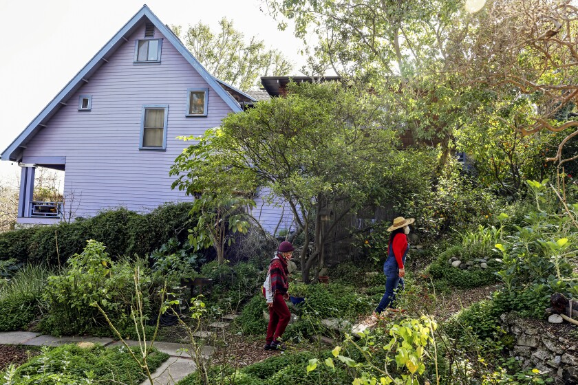 Two women walk on a greenery-lined path beside a house.