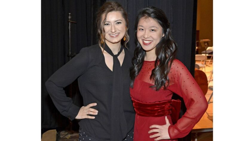Fashion design student Katrin Divinets, left, with harpist Alyssa Katahara wearing the red silk and