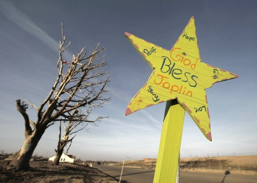 An inspirational sign at an intersection in a Joplin, Mo., neighborhood that was destroyed in May by a tornado.