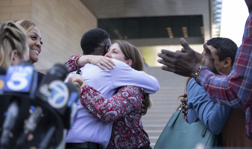 Dane Brown hugs Assistant U.S. Atty. Lindsay Bailey outside a Los Angeles federal courthouse.