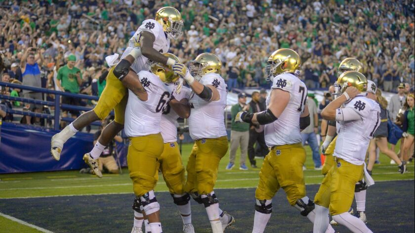 Dexter Williams #2 of the Notre Dame Fighting Irish is lifted in celebration after scoring a touchdown in the 1st half against the Navy Midshipmen at SDCCU Stadium on October 27, 2018 in San Diego, California.