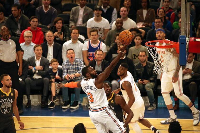 Tim Hardaway Jr. (c) de New York Knicks intenta anotar contra Golden State Warriors durante su juego de la NBA en el Madison Square Garden en Nueva York (EE.UU.). EFE