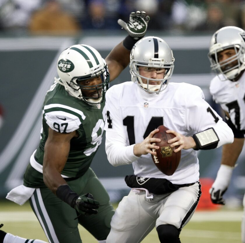 New York Jets outside linebacker Calvin Pace (97) closes in moments before sacking Oakland Raiders quarterback Matt McGloin (14) during the second half of an NFL football game, Sunday, Dec. 8, 2013, in East Rutherford, N.J. The Jets won 37-27. (AP Photo/Kathy Willens)