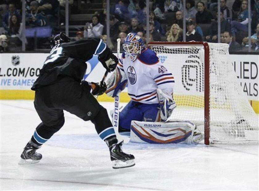 Edmonton Oilers goalie Devan Dubnyk (40) deflects a shot on goal by San Jose Sharks center Scott Gomez (23) during the first period of an NHL hockey game in San Jose, Calif., Thursday, Jan. 31, 2013. (AP Photo/Tony Avelar)