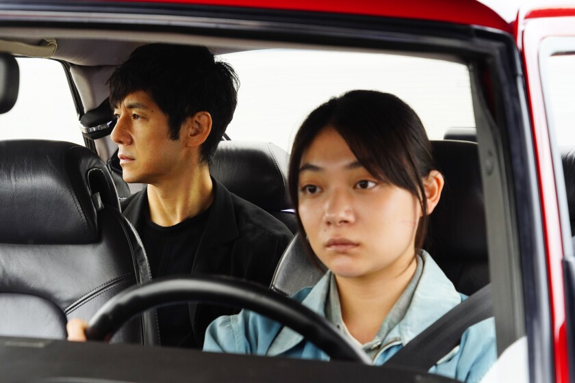 A female driver and a male back-seat passenger in a car.