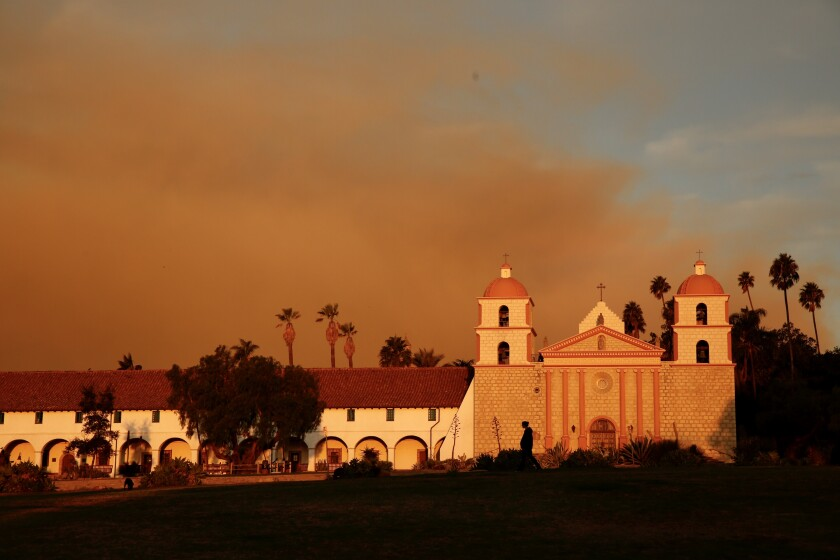 Smoke rises behind the Santa Barbara Mission on Tuesday morning from the Cave fire.