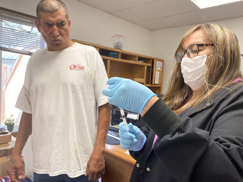 وقتی سوزن واکسیناسیون توسط یک پرستار آماده می شود ، مرد می لرزد.