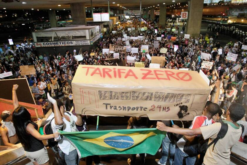 """Brazilians hold a bus-shaped poster that reads in Portuguese, """"Zero fares, transport 24 hours,"""" during a march June 19 demanding free public transit."""