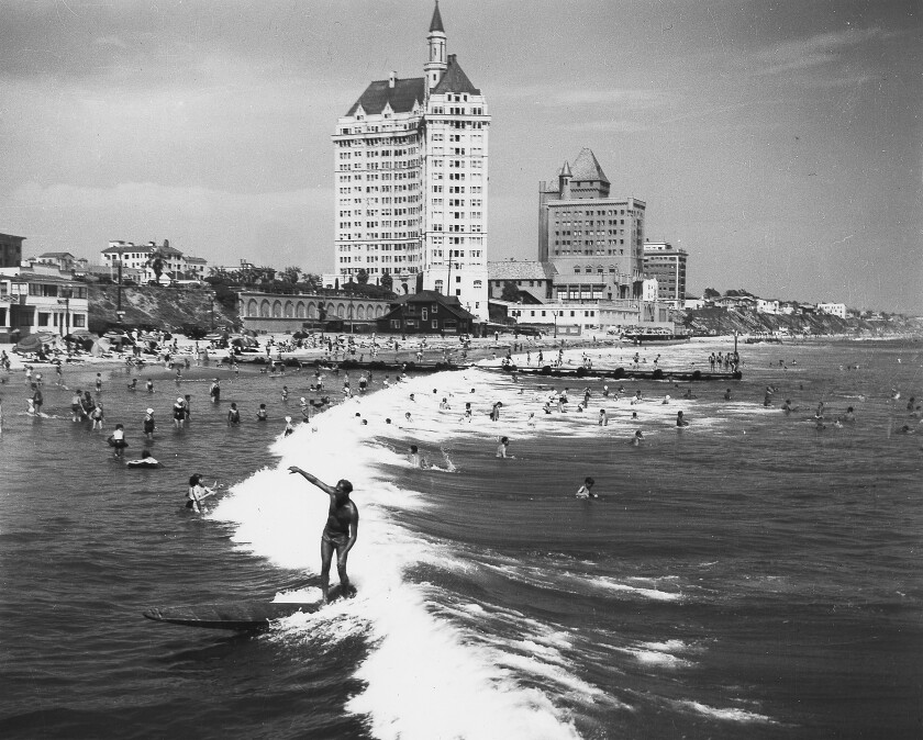 1938 image of a surfer riding a wave before the Long Beach breakwater was constructed