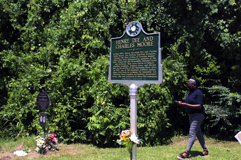 A woman who attended a dedication ceremony for a new Mississippi historical marker walks by the marker on Thursday, July 15, 2021, in Meadville, Miss. The sign provides information about the 1964 Ku Klux Klan kidnapping and killing of Charles Eddie Moore and Henry Hezekiah Dee. Law enforcement officers found the bodies of the two Black teenagers in the Mississippi River while searching for three civil rights workers who had been kidnapped and killed by the Klan in June 1964 in a different part of Mississippi. A reputed Klansman, James Ford Seale, was convicted in 2007 in federal court in Jackson, Miss., on charges of kidnapping and conspiracy related to the fatal abduction of Dee and Moore. Seale died in prison in 2011. (AP Photo/Emily Wagster Pettus)