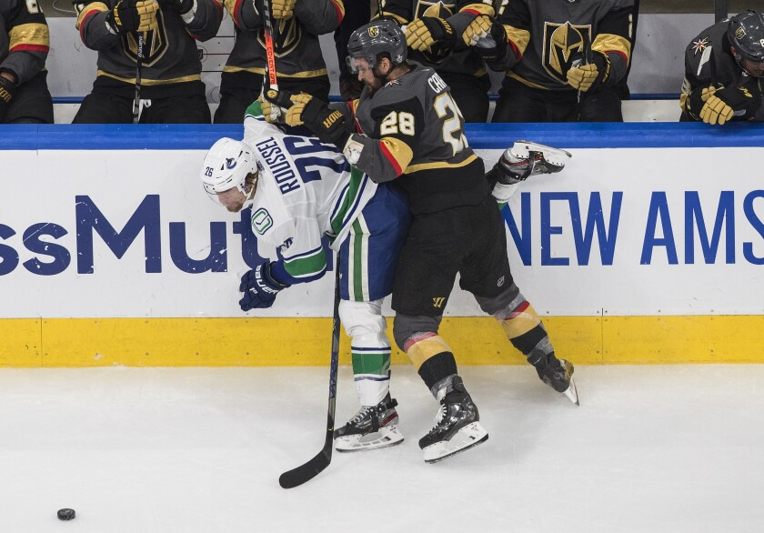 Vancouver Canucks' Antoine Roussel (26) is checked by Vegas Golden Knights' William Carrier (28) during second-period NHL Western Conference Stanley Cup playoff hockey action in Edmonton, Alberta, Friday, Sept. 4, 2020. (Jason Franson/The Canadian Press via AP)