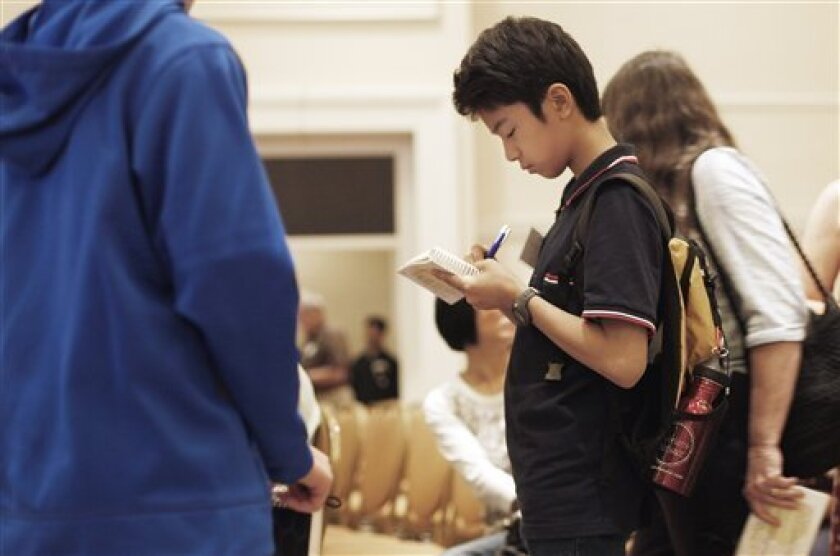 Yuichi Yoshioka, 12, from Tokyo, Japan, exchanges autographs with other spelling bee participants after the written first round test of the 2011 Scripps National Spelling Bee, Tuesday, May 31, 2011, at the Gaylord National Resort and Convention Center in National Harbor, Md. (AP Photo/Pablo Martinez Monsivais)