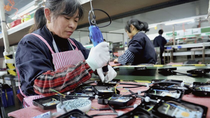 In this Saturday, March 30, 2019, photo, workers assemble LED lights at a factory in Yushan county i