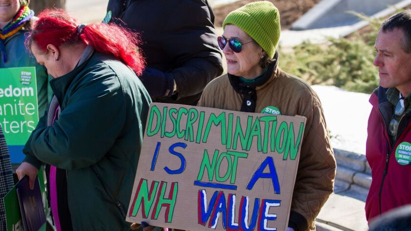 "Katharine Daly of Dunbarton, N.H., holds a sign that reads ""Discrimination is not a NH value"" during"