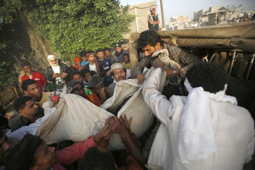 Varias personas manipulan el cadáver de una víctima que encontraron entre los escombros de casas destruidas por los ataques aéreos dirigidos por Arabia Saudí contra los hutíes en Yemen el 13 de julio del 2015. (AP Foto/Hani Mohammed)