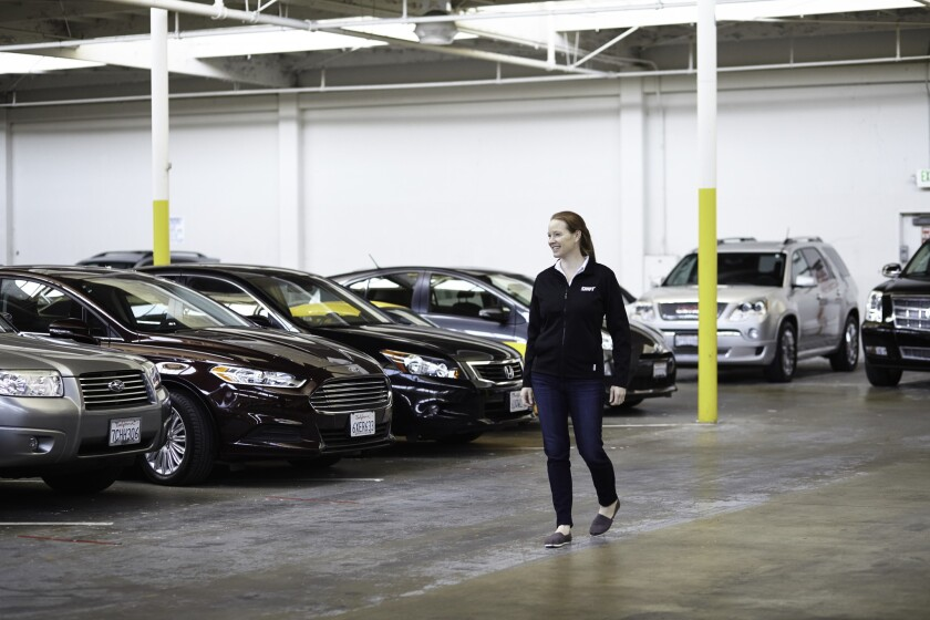 Shift's chief operating officer, Minnie Ingersoll, walks through the Hub, a warehouse where the company photographs and stores the cars until they are sold.