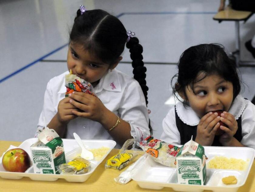 Brenda Segura (izda) y Citlaly Gonzalez, estudiantes de la Escuela McCormick de la Villita, un barrio hispano de Chicago (EEUU), comen frutas y verduras durante el almuerzo. EFE/Archivo
