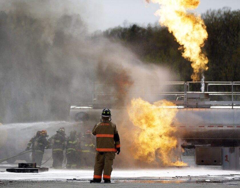Firefighters douse flames on a tanker truck in a simulated oil spill drill Wednesday in Albany, N.Y.