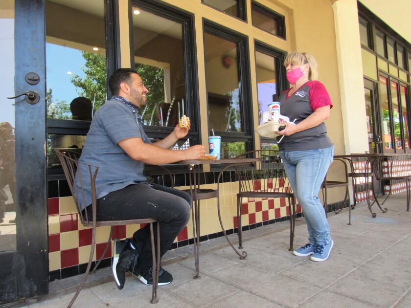 Shauhin Salehyan enjoys a sandwich outdoors with Main Street Donuts & Deli employee Tammi Harold in El Cajon.