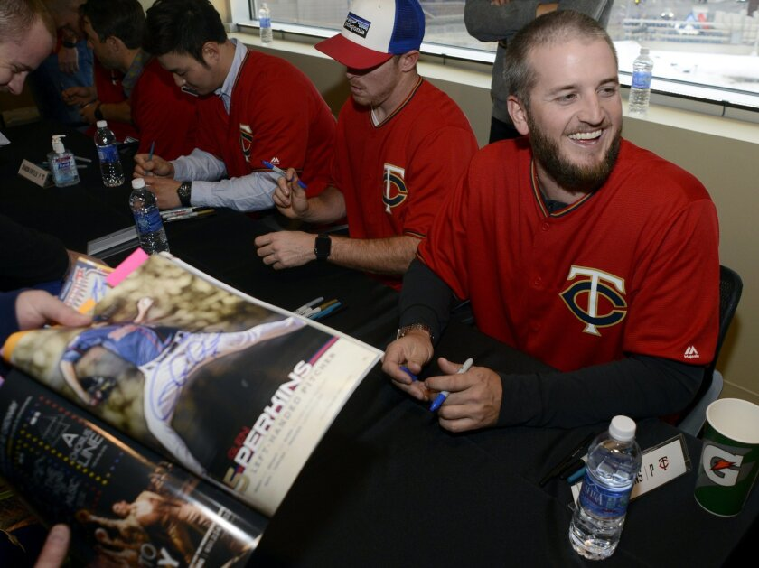CORRECTS DATE TO JAN. 29 - Minnesota Twins' Glen Perkins signs an autograph during the baseball team's TwinsFest on Friday, Jan. 29, 2016, in Minneapolis. (AP Photo/Hannah Foslien)