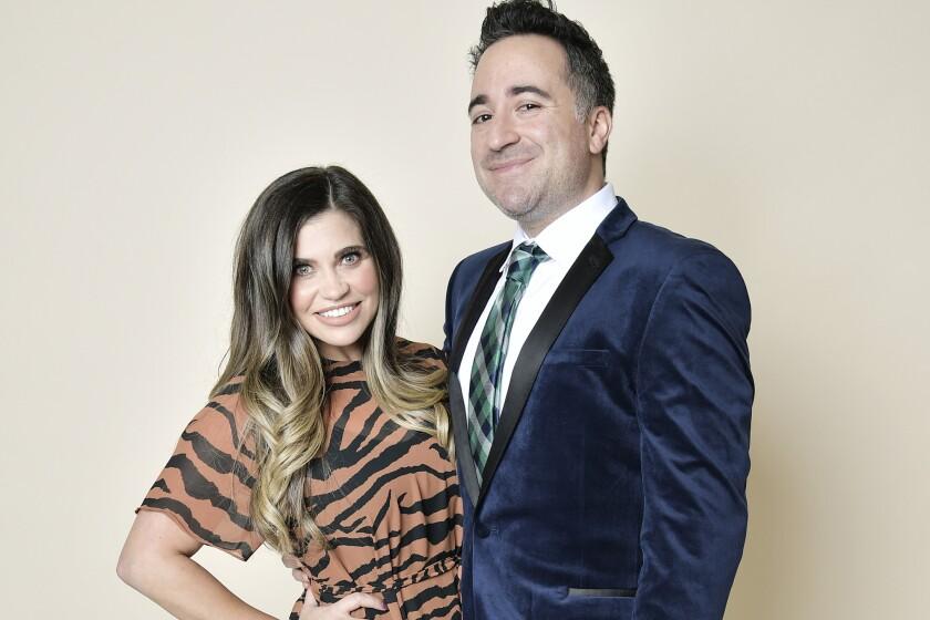 Jensen Karp in a blue tuxedo jacket with wife Danielle Fishel in an animal print dress