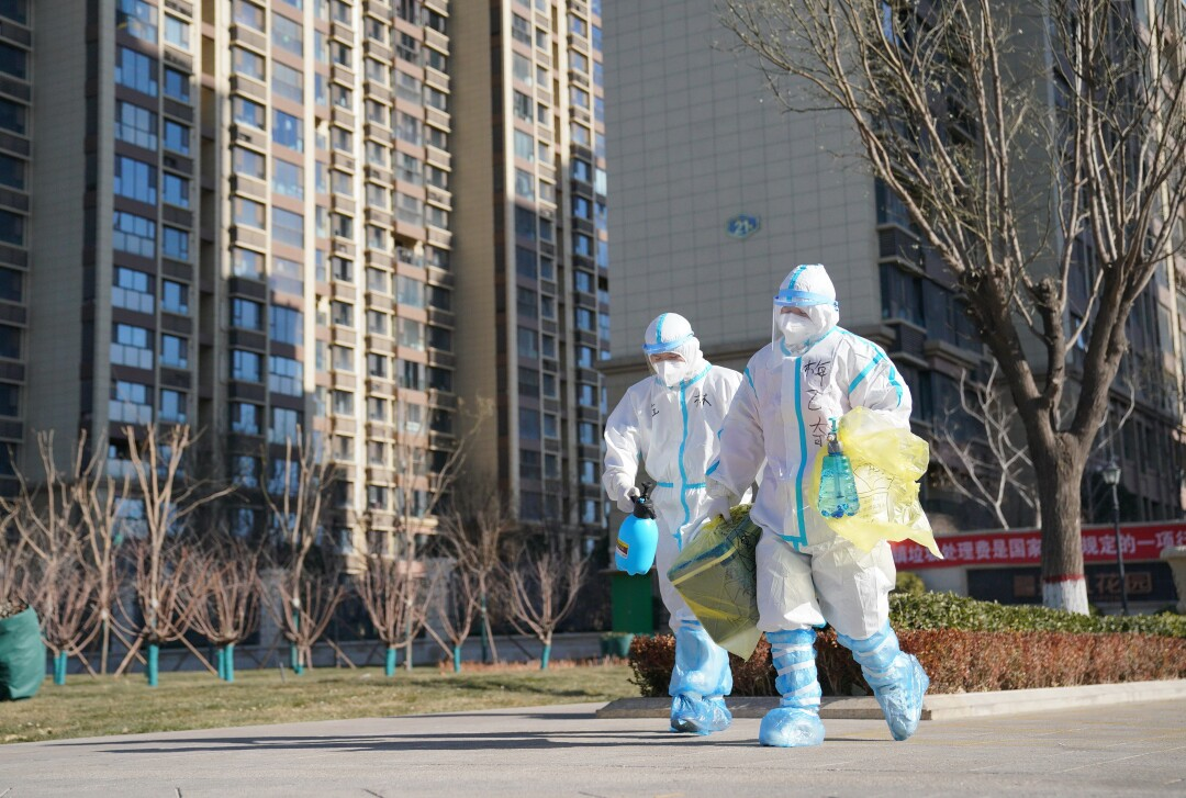Workers carry a container of coronavirus test samples outside a neighborhood in Shijiazhuang, China.
