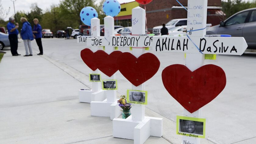 Four wooden crosses stand as a memorial for the four shooting fatalities outside a Waffle House restaurant in Nashville on Wednesday.