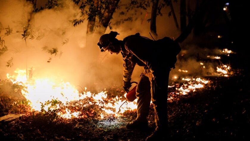 Firefighter Brandon Tolp works to prevent flames from crossing Highway 29, north of Calistoga, Calif.