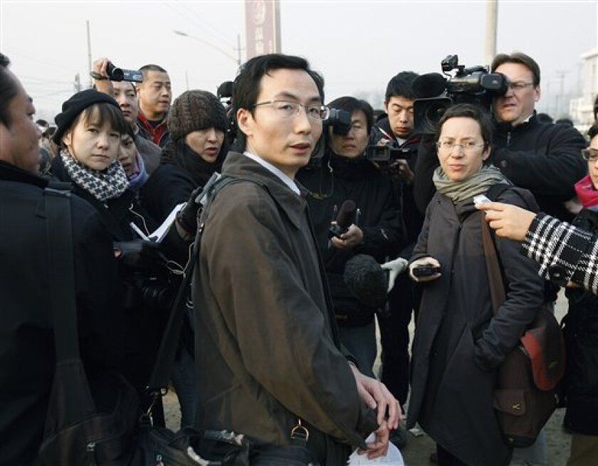 Li Fangping, center, lawyer of artist Wu Yuren speaks to journalists as he arrives at the Wenyuhe Court in Beijing, China Wednesday, Nov. 17, 2010. Wu was detained and charged after he helped organize protests near Tiananmen Square against some urban development schemes in the 798 artist area of Be