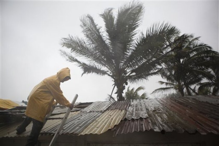 """Gumercindo Gomes, 48, tries to fix the roof of a bar at the Playa Azul, or """"Blue beach"""" as Tropical Storm Arlene arrives in Tuxpan, Mexico, Thursday, June 30, 2011. Tropical Storm Arlene struck land near Cabo Rojo, a cape just off the mainland between the cities of Tampico and Tuxpan. It had maximu"""