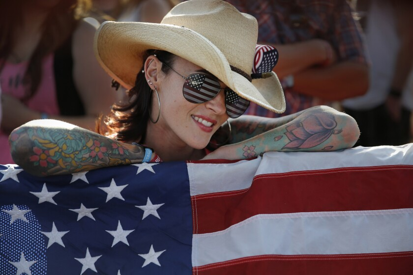 Lindsay German of Ventura, sporting American flag sunglasses while toting a large U.S. flag, listens to music at the Mane Stage during the first day of the 10th Stagecoach Country Music Festival.