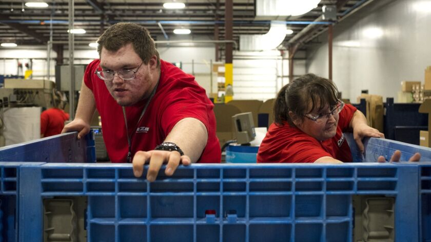 Colton Channon, left, and Tracy Miller open a crate at Dee Zee Manufacturing.
