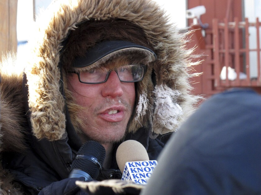 FILE - In this March 12, 2012 file photo, musher Brent Sass speaks to reporters after completing the nearly 1,000 mile Iditarod Trail Sled Dog Race in Nome, Alaska. Sass, coming off back-to-back wins in another long-distance sled dog race, was the first to reach the halfway point of this year's Iditarod Trail Sled Dog Race. The native of Minnesota living near the Alaska community of Eureka arrived late Wednesday night, March 11, 2020 with 13 dogs in harness at the checkpoint in Cripple, where Sass said he planned to take his mandatory 24-hour rest period. (AP Photo/Mark Thiessen, File)