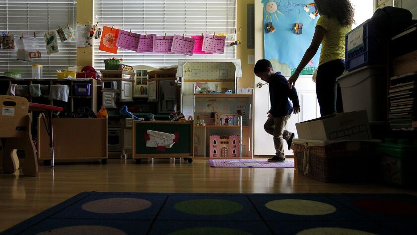 LOS ANGELES-CA-MARCH 27, 2014: A child is lead inside at day care at Alexandria House, which provide