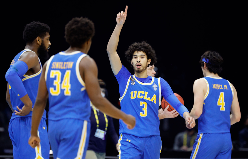 UCLA's Johnny Juzang points up while walking toward teammates